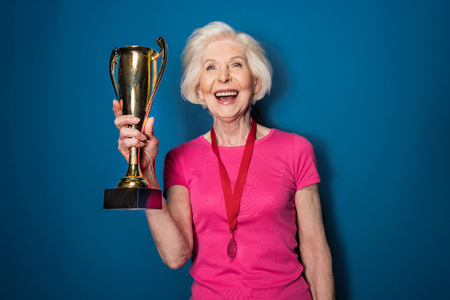78654109 - excited senior woman in sportswear holding trophy